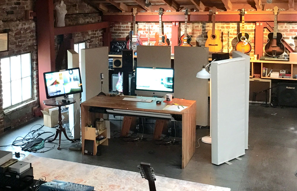 GIK Acoustics Freestand Akustikwand in large brick-wall studio with desk and computer screen